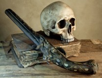 Vintage photo of a skull and pistol as in an old master painting